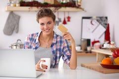 Усмехаясь покупки женщины онлайн используя компьютер и Стоковые Фото
