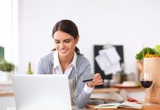 Усмехаясь покупки женщины онлайн используя компьютер и Стоковое Изображение RF