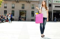 Усмехаясь покупки молодой женщины в городе стоковое изображение