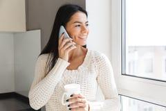 Усмехаясь положение женщины брюнета на окне внутри помещения стоковое изображение rf