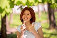 Усмехаясь положение женщины под деревьями в парке или лесе с большими мороженым и показывать большим пальцем руки вверх Наслаждат стоковое фото