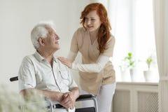 Усмехаясь попечитель помогая выведенному из строя старшему человеку в кресло-коляске стоковая фотография