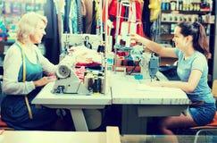2 усмехаясь портноя женщин работая с швейными машинами Стоковая Фотография