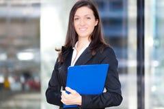 Усмехаясь портрет бизнес-леди держа некоторые документы стоковые изображения rf