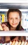 Усмехаясь портрет девушки через книжные полки Стоковое Фото