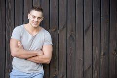 Усмехаясь портрет молодого человека перед деревянной стеной Стоковые Изображения
