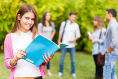 Усмехаясь портрет студента держа книгу Стоковые Фотографии RF