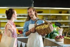 Усмехаясь поставщик держа корзину картошек пока взаимодействующ с женщиной Стоковые Фотографии RF