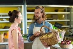 Усмехаясь поставщик держа корзину картошек пока взаимодействующ с женщиной Стоковое Фото