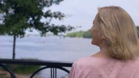 Усмехаясь постаретая женщина наслаждаясь природой парка лета, релаксацией outdoors, безмятежность сток-видео