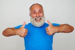 Усмехаясь постаретый человек давая 2 большого пальца руки вверх против белой предпосылки Стоковое Фото
