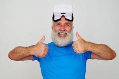 Усмехаясь постаретый человек в VR-шлемофоне на его голове давая 2 большого пальца руки вверх Стоковые Фото