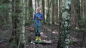 Усмехаясь потерянная женщина подборщика гриба держа мобильный телефон с gps в лесе сток-видео