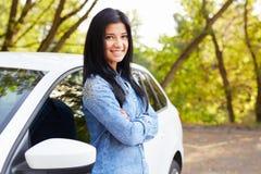 Усмехаясь положение и склонность женщины на автомобиле Стоковое Фото