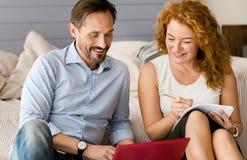 Усмехаясь положительные пары работая совместно дома Стоковая Фотография