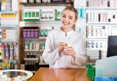Усмехаясь положительный женский представлять аптекаря Стоковые Фото