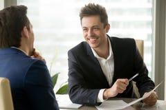 2 усмехаясь положительных бизнесмена смеясь над, имеющ потеху во время шины Стоковая Фотография