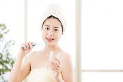Усмехаясь полотенце азиатской женщины суша на головной держа зубной щетке Стоковая Фотография