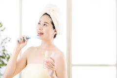 Усмехаясь полотенце азиатской женщины суша на головной держа зубной щетке Стоковое Изображение RF