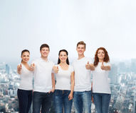 Усмехаясь подростки в футболках показывая большие пальцы руки вверх Стоковые Фото