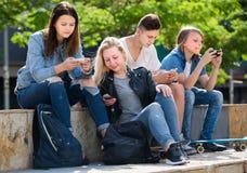 Усмехаясь подростки играя с мобильными телефонами Стоковая Фотография RF