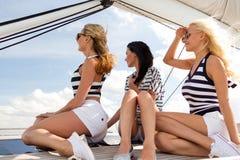 Усмехаясь подруги сидя на палубе яхты Стоковое Изображение RF