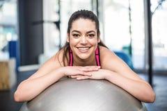 Усмехаясь подходящая склонность женщины на шарике фитнеса Стоковая Фотография RF