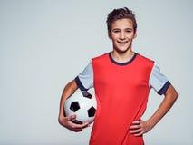 Усмехаясь предназначенный для подростков мальчик в sportswear держа футбольный мяч стоковые фотографии rf