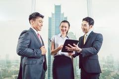 Усмехаясь предприниматели смотря цифровой планшет стоковые фото