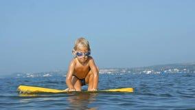 Усмехаясь прелестный ребенок наслаждаясь bodyboard голубого моря surfboarding движение медленное сток-видео