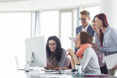 Усмехаясь предприниматели работая совместно на столе переговоров Стоковое фото RF