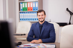 Усмехаясь предприниматель в деловом костюме на его месте работы Стоковое Изображение RF