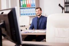 Усмехаясь предприниматель в деловом костюме на его месте работы Стоковые Изображения