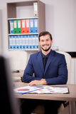 Усмехаясь предприниматель в деловом костюме на его месте работы Стоковое Изображение