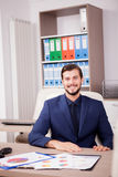 Усмехаясь предприниматель в деловом костюме на его месте работы Стоковая Фотография