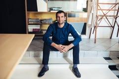 Усмехаясь предприниматель сидя в большой студии работы Стоковое фото RF