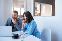 2 усмехаясь предпринимателя работая на компьтер-книжке в офисе Стоковое Изображение