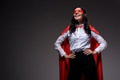 усмехаясь привлекательная супер коммерсантка в красных накидке и маске стоковое фото