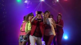 Усмехаясь привлекательные люди принимая selfie на ночной клуб с музыкой в предпосылке дыма ( сток-видео