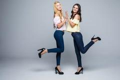 2 усмехаясь привлекательных подруги белокурая и брюнет имеют потеху на белой предпосылке Стоковые Фотографии RF