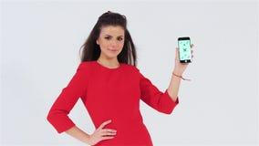 Усмехаясь привлекательная девушка показывая умный телефон с держателем места акции видеоматериалы