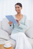 Усмехаясь привлекательная женщина используя ее планшет Стоковое Изображение