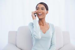 Усмехаясь привлекательная женщина на телефоне сидя на уютной софе стоковое фото rf