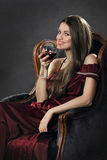 Усмехаясь привлекательная женщина представляет с стеклом красного вина Стоковые Фотографии RF