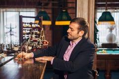 Усмехаясь привлекательный молодой бармен обтирая стекла и говоря к человеку в баре Стоковое Изображение RF