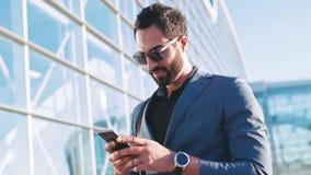 Усмехаясь привлекательный молодой человек в стильных солнечных очках использует его телефон, смотрит вокруг, будет осадкой, после видеоматериал