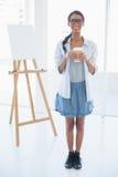 Усмехаясь привлекательный художник держа чашку кофе стоковое фото