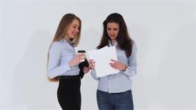 2 усмехаясь привлекательных девушки офиса выпивая кофе и пустое A4 покрывают сток-видео