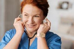 Усмехаясь приятный доктор используя ее стетоскоп стоковая фотография rf