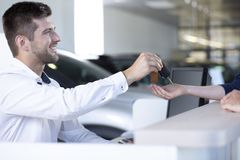 Усмехаясь продавец автомобиля давая ключи к покупателю в общаться салон стоковое изображение